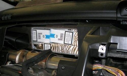 Сигареты под передней панелью машины в салоне