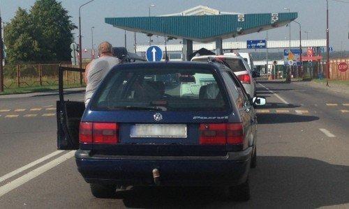 Водитель толкает машину в очереди у границы