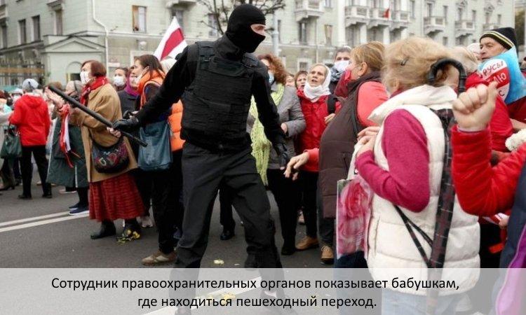 Сотрудник правоохранительных органов показывает бабушкам, где находиться пешеходный переход.