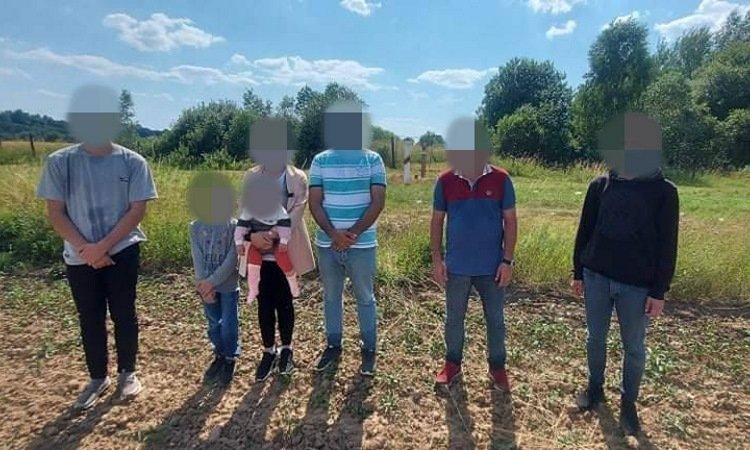 Нелегальные мигранты на фоне пограничного столба в Литве